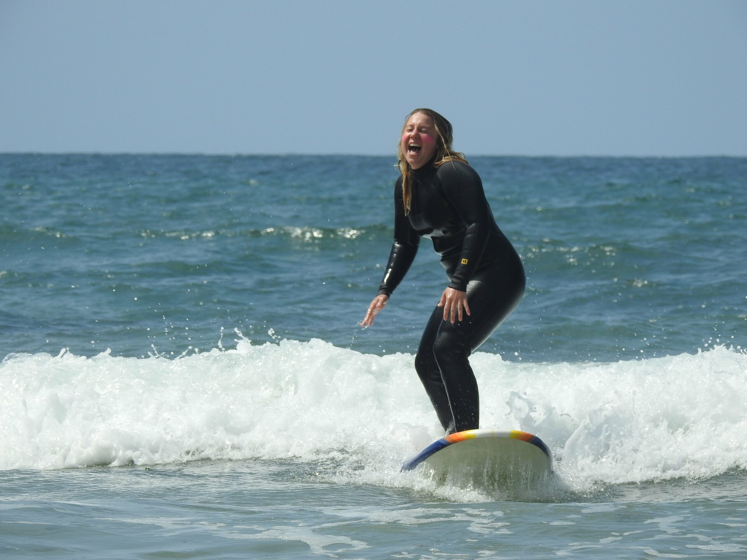 woman surfing and laughing